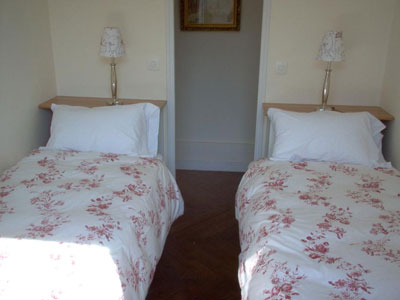 The second bedroom has two twin beds, and views of the Place des Vosges
